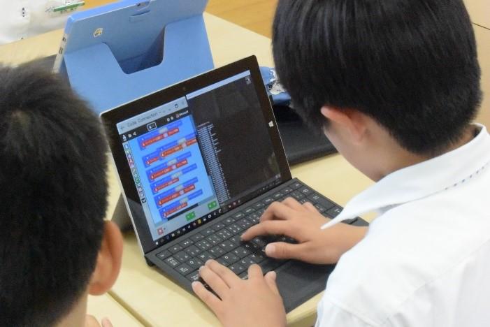自分たちがつくった作品を説明するロボットをプログラミングする子ども達
