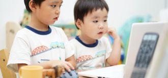 インターネットゲームを通じて海外の子どもと英語でコミュニケーションする日本人兄弟のイメージ写真